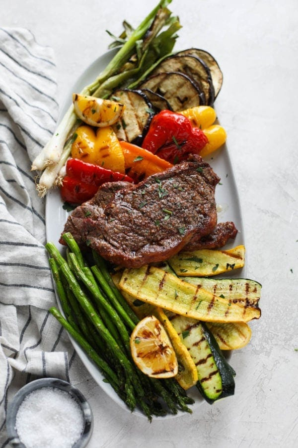 A white platter filled with grilled vegetables and a perfectly grilled steak in the center.