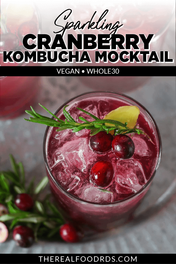 Overhead shot of sparkling cranberry kombucha mocktail in an old-fashioned glass and garnished with fresh cranberries, rosemary sprig, and fresh ginger.