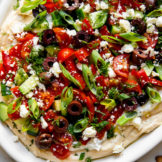 A layered Greek-inspired hummus dip topped with cucumber, kalamata olives, cherry tomatoes, and fresh dill.