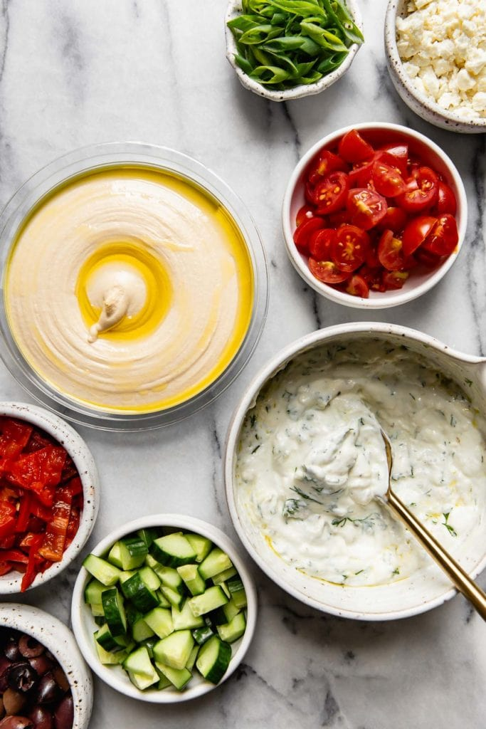 Greek dip Ingredients in white, speckled bowls.