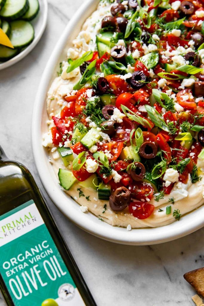 Greek Hummus Dip served on a large, white platter. A thick layer of hummus topped with a layer of Tzatziki, cucumber, tomatoes, feta, olives, green onion, herbs and drizzled with Primal Kitchen olive oil.