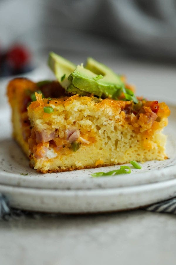 A close up view of pancake-based egg breakfast casserole to show the great texture. Topped with sliced avocado.