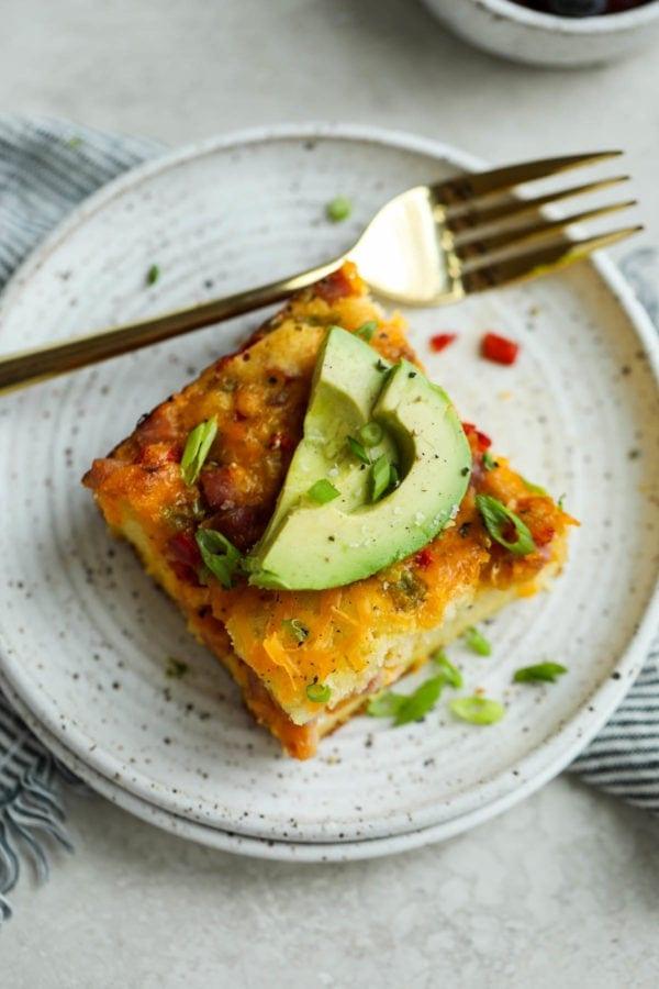 A large slice of breakfast casserole on a speckled plate and topped with sliced avocado.