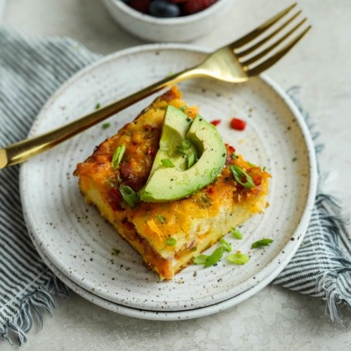 A piece of Western-style breakfast casserole on a speckled plate and topped with sliced avocado.