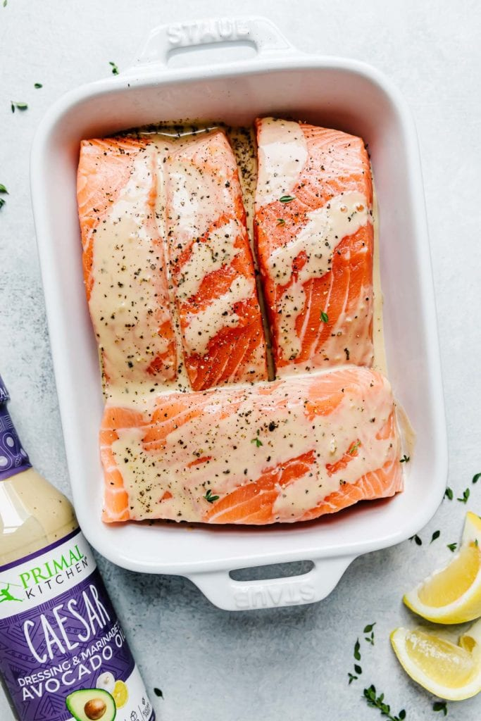 Three salmon fillets in a white baking dish with caesar dressing over the top
