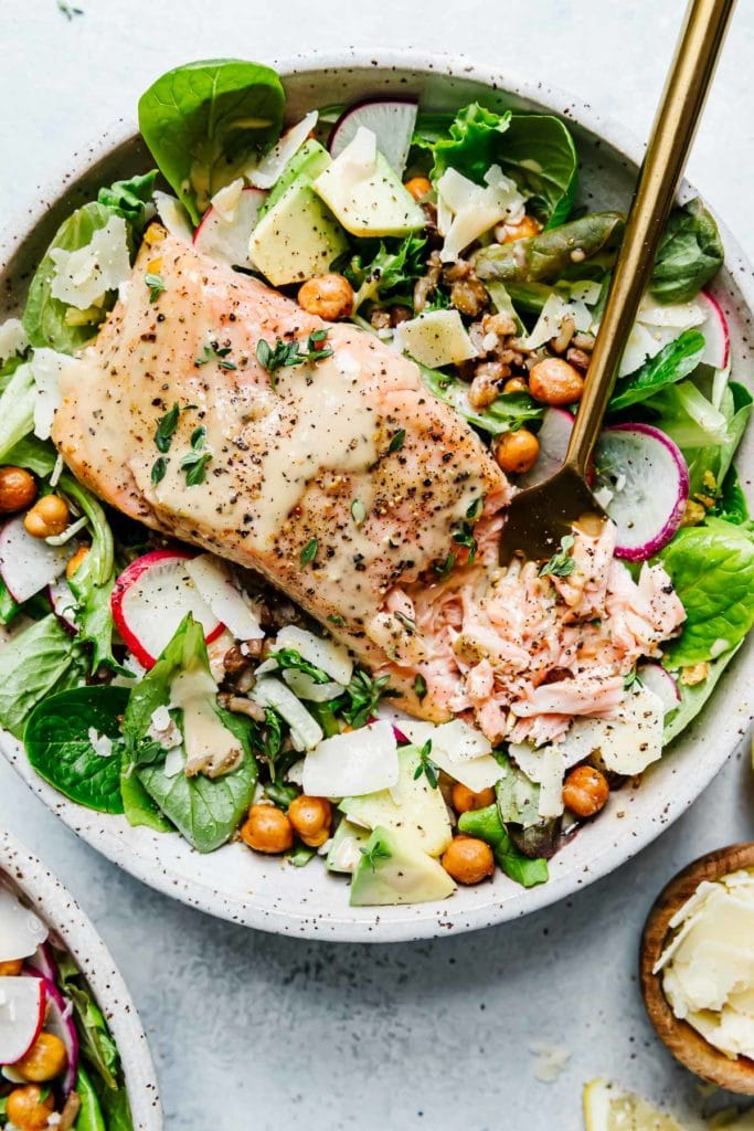 Caesar Salmon Salad Grain Bowl in a speckled stone bowl with greens, avocado, crispy chickpeas and flaky salmon.