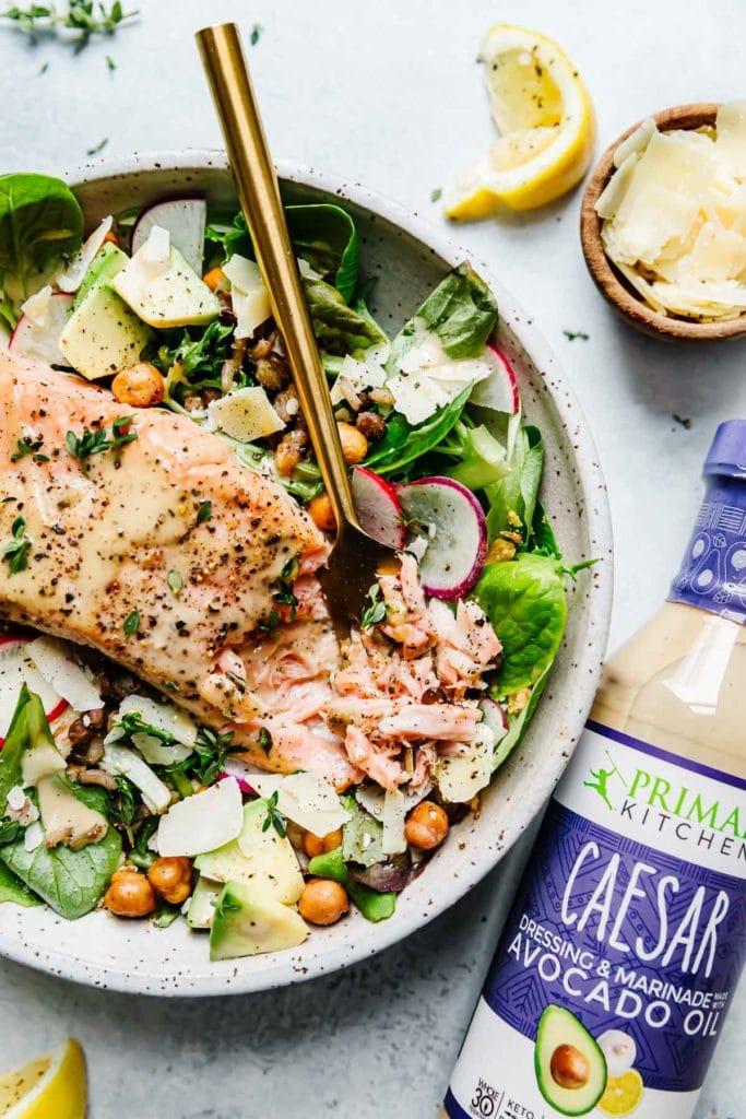 Caesar Salmon Salad Grain Bowl in a speckled stone bowl with greens, avocado, crispy chickpeas, flaky salmon and a bottle of caesar dressing.
