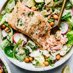 Overhead view of salmon caesar salad grain bowl in a speckled bowl