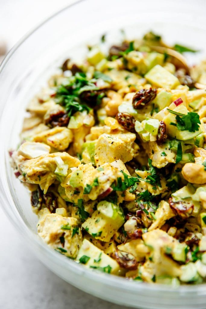 All ingredients for curry chicken salad mixed together in a bowl ready for serving.