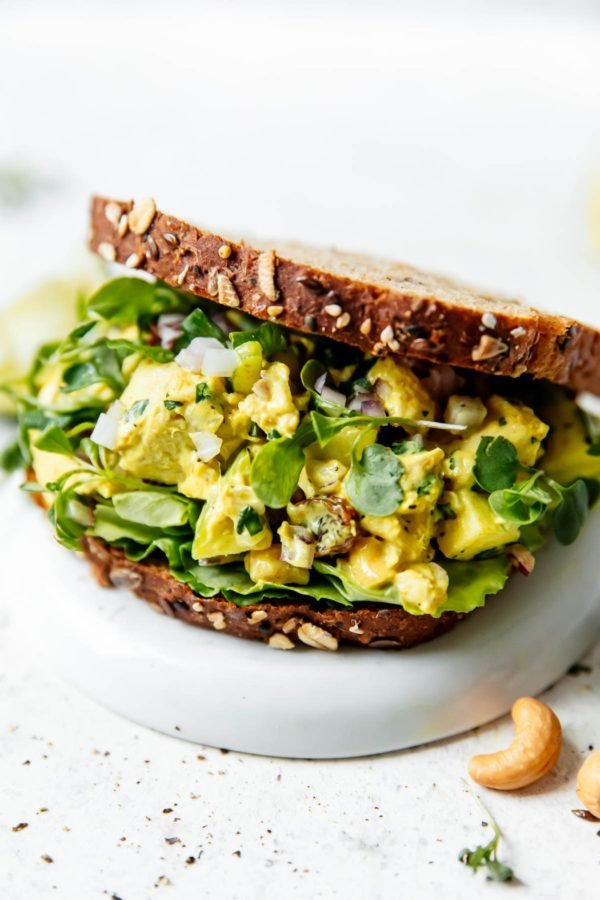 Curry chicken salad sandwich with lettuce and sprouts and cashews