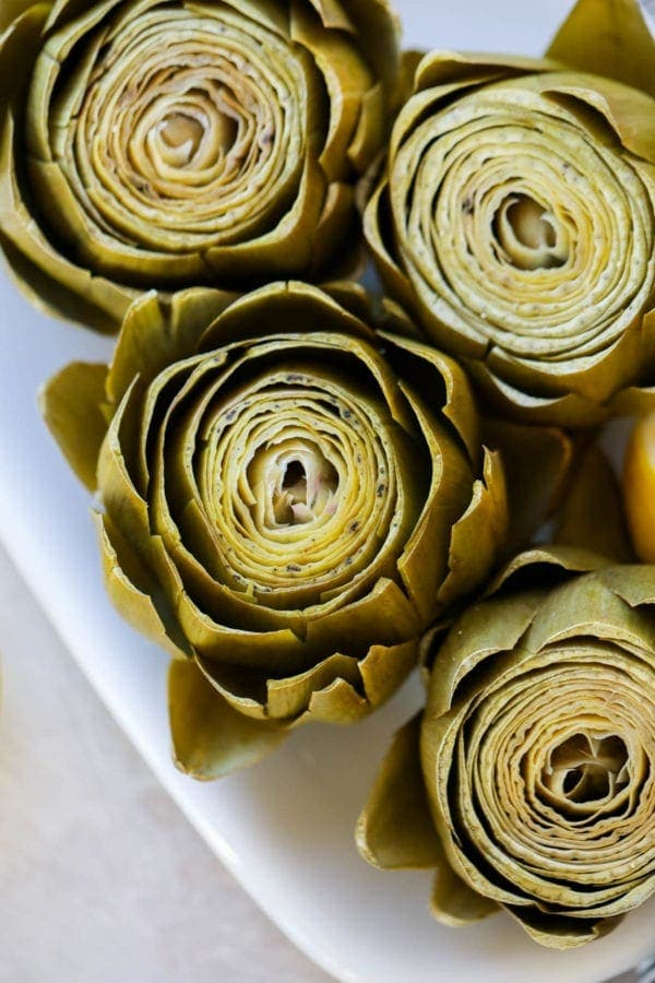 Freshly cooked artichokes on a white platter