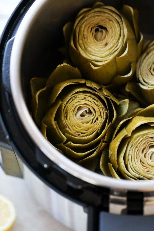 A close up view of freshly cooked artichokes in an Instant Pot