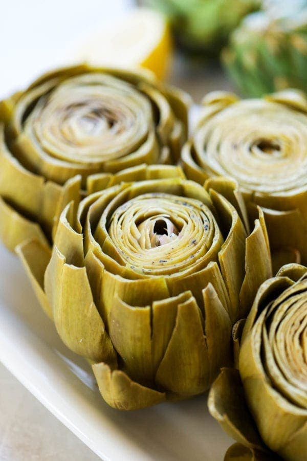 Freshly cooked artichokes with petals peeling away from the center on a white platter