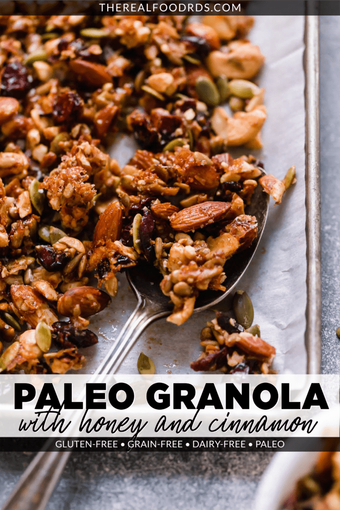 A spoonful of Paleo granola made with nuts and seeds on a baking sheet ready for serving.