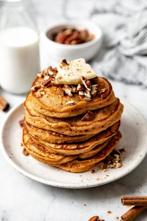 A large stack of fluffy gluten free sweet potato pancakes on a white plate topped with a pad of butter and chopped pecans