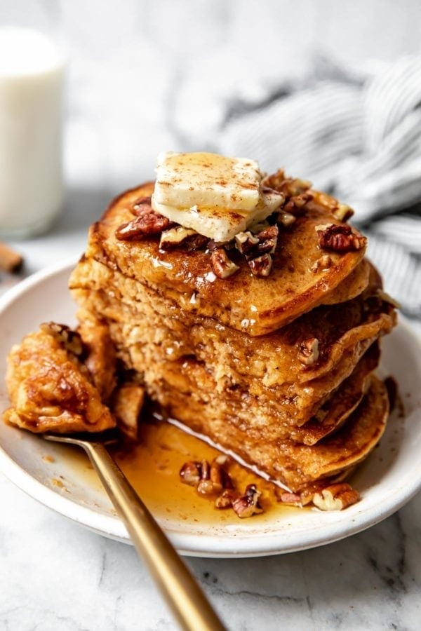 A stack of gluten free fluffy sweet potato pancakes cut in half to show the fluffy inside texture.