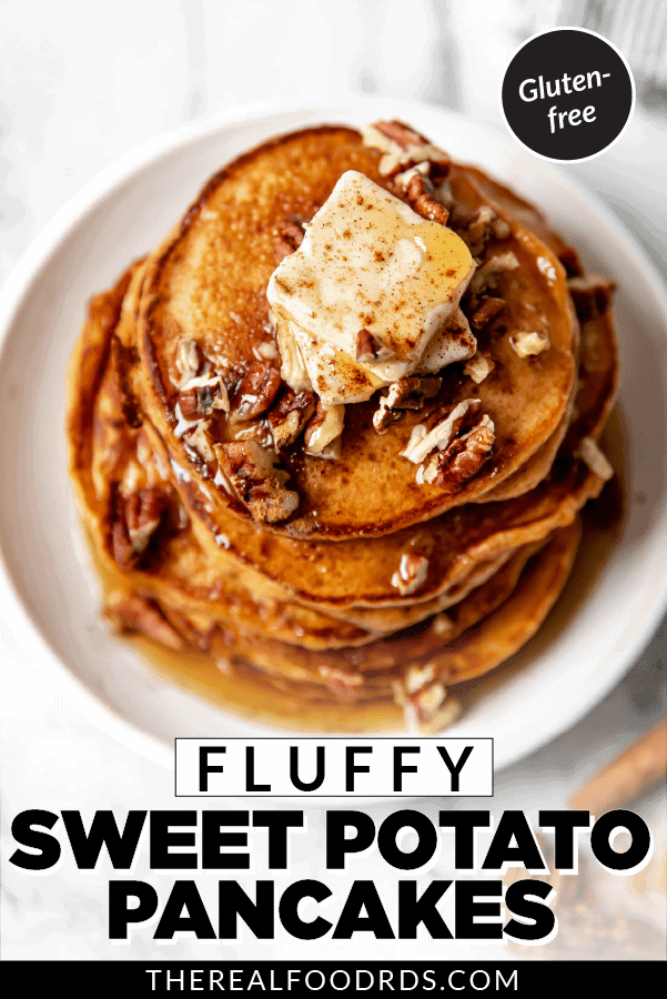 Overhead view of a stack of fluffy sweet potato pancakes on a white plate topped with butter, pecans, and maple syrup.
