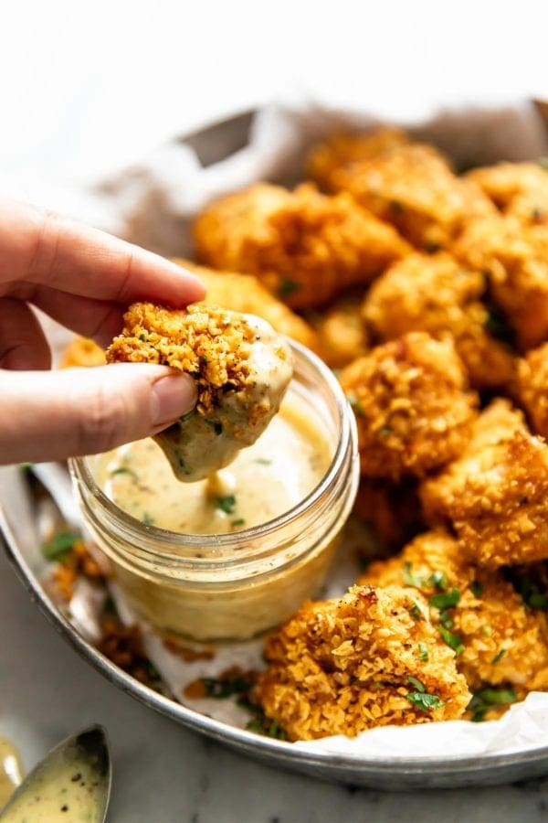 A baked chicken nugget being dipped in homemade honey mustard sauce