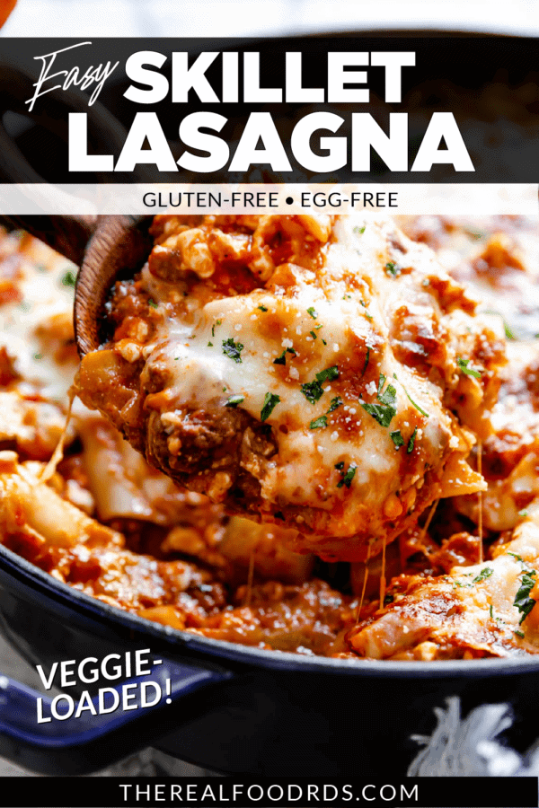 Easy cheesy skillet lasagna being scooped out of a cast iron skillet with a wooden spoon. Text overlay with title of recipe for Pinterest.