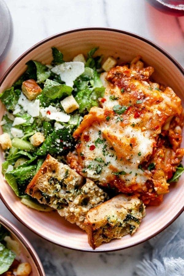 Easy Skillet Lasagna served in a bowl on top of romaine lettuce with shaved parmesan cheese