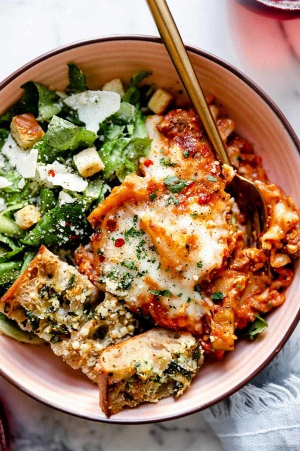 Easy Skillet Lasagna served in a ceramic bowl on top of Romaine lettuce with garlic bread and shaved parmesan on the side