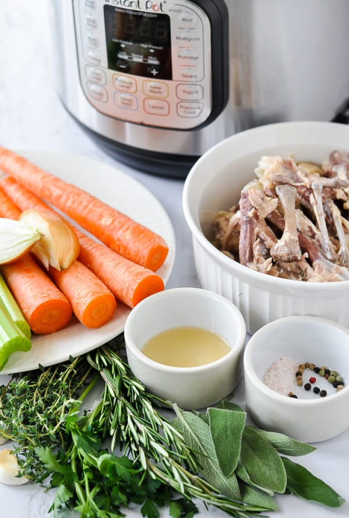 All ingredients for bone broth in white bowls in front of an Instant Pot