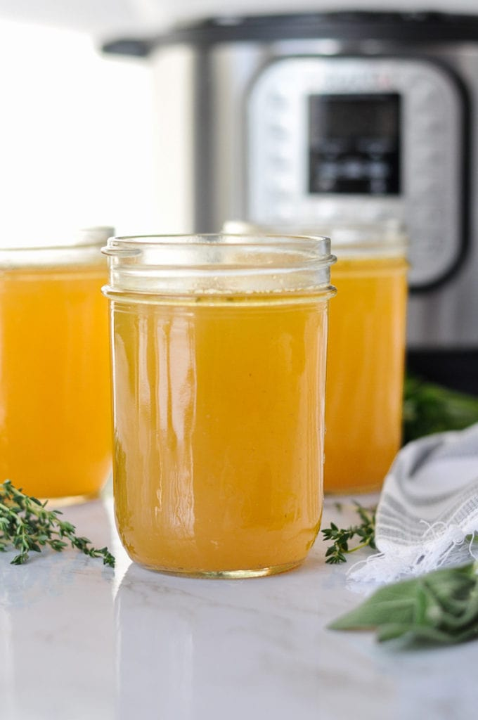 Three mason jars filled with Instant Pot bone broth with fresh herbs scattered around them