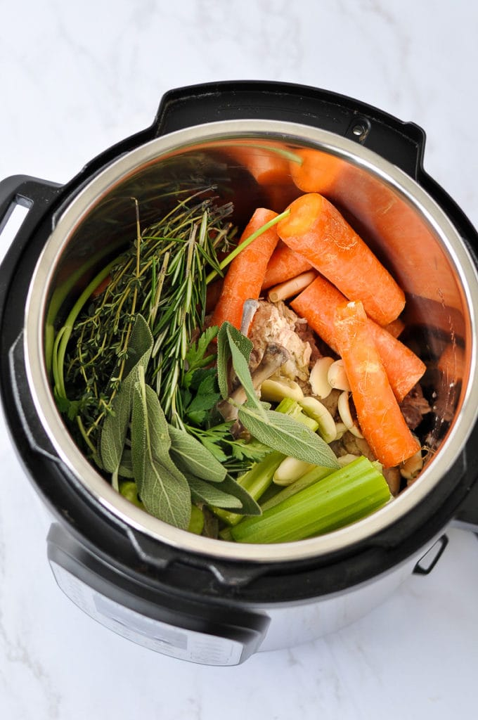 Roughly chopped root vegetables, fresh herbs, chicken bones, and garlic in an Instant Pot ready to make bone broth