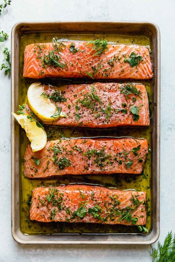 Four salmon fillets marinating in a baking sheet topped with dill weed and lemon wedges
