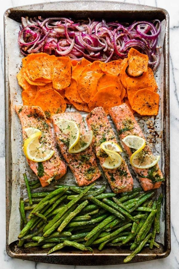 Baked salmon fillets, green beans, sweet potato rounds, and purple onions freshly baked on a baking sheet