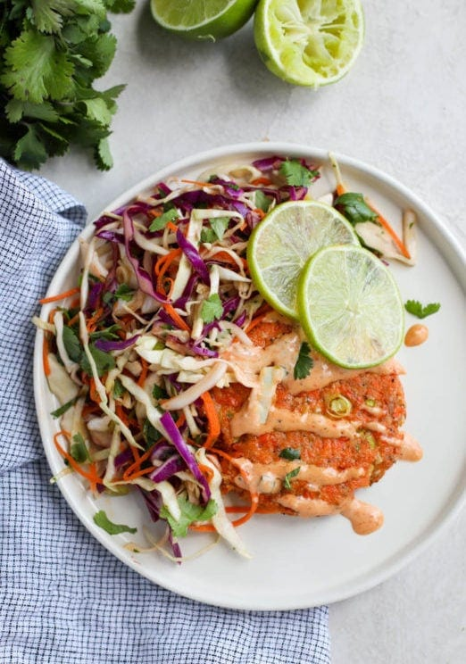 A grilled salmon burger on a white plate topped with cabbage slaw, chipotle sauce, and limes