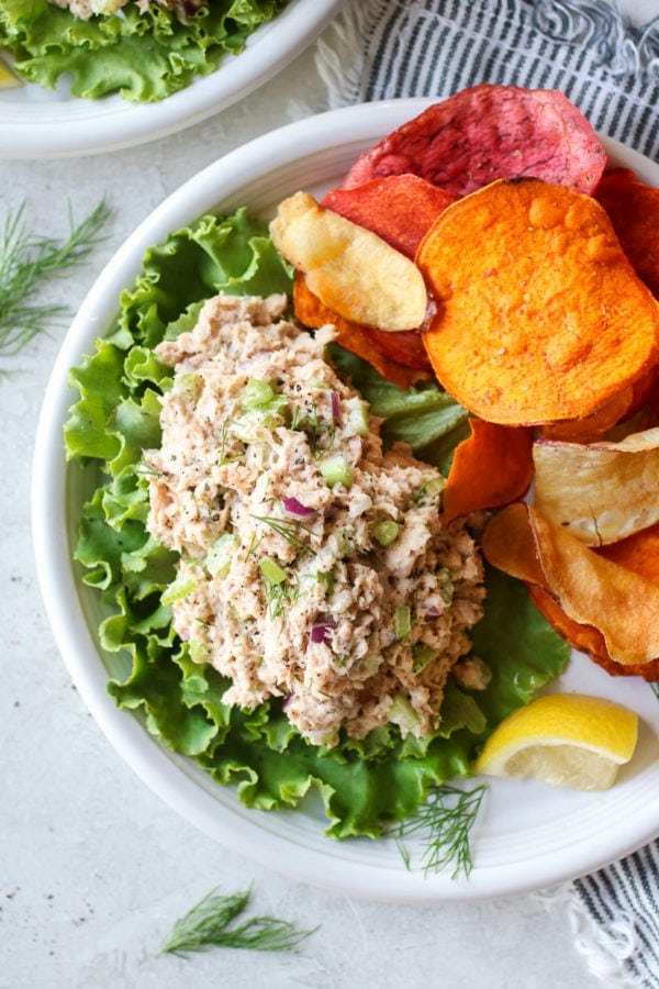 Quick and easy salmon salad served on a bed of lettuce with sweet potato chips and a lemon wedge on the side