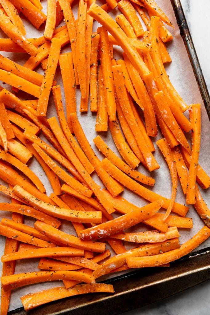 Carrot fries spread out on a baking sheet ready for the oven