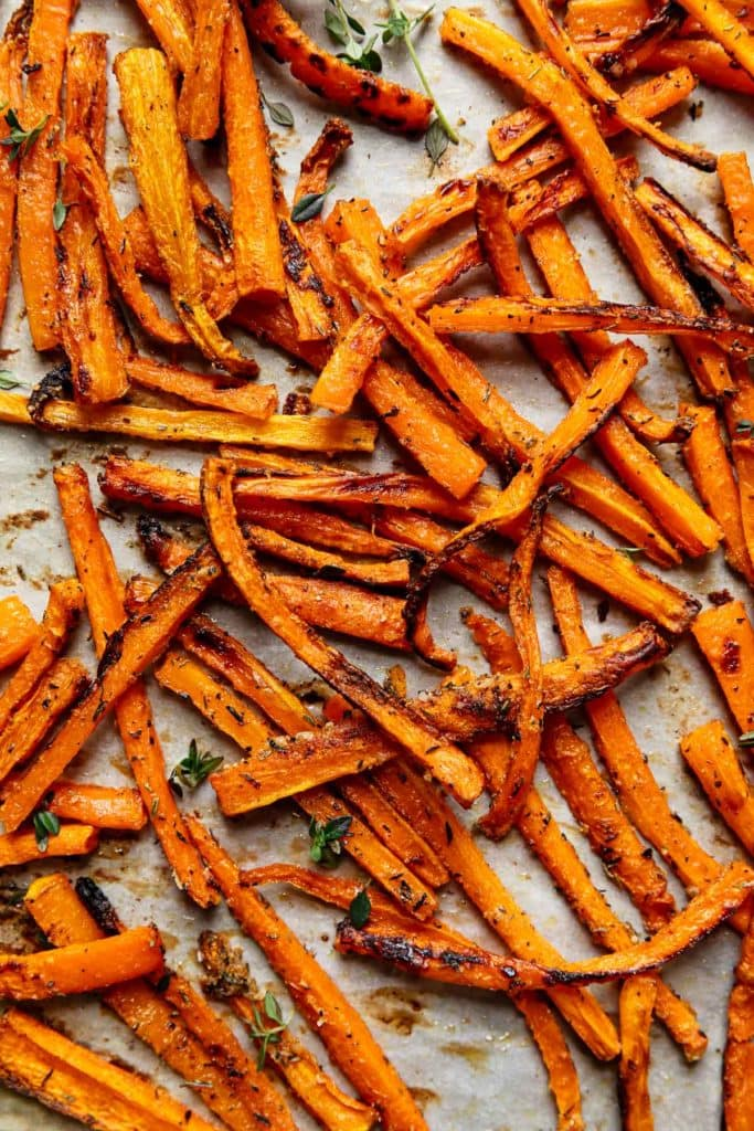 Fresh baked oven carrot fries on a baking sheet seasoned with thyme and sea salt