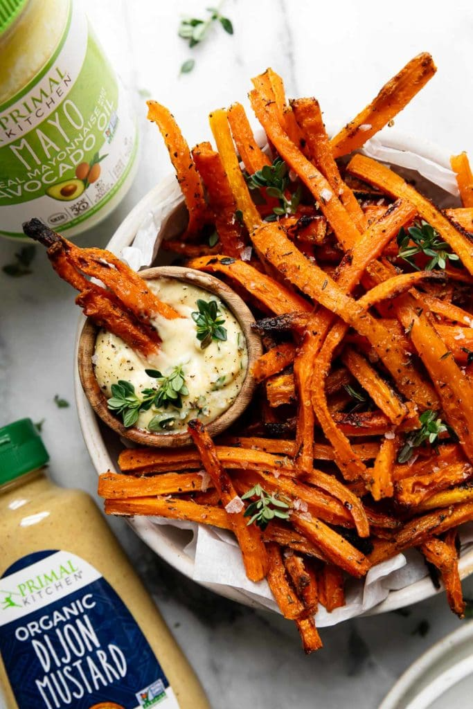 Baked carrot fries sprinkled with fresh thyme and sea salt being dipped in a wooden bowl filled with dijon-thyme aioli