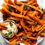 A large bowl of oven baked carrot fries with a side of dijon-thyme aioli