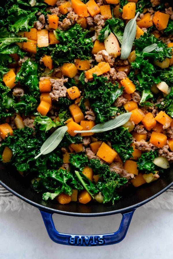 A skillet filled with butternut squash, kale, and sausage hash