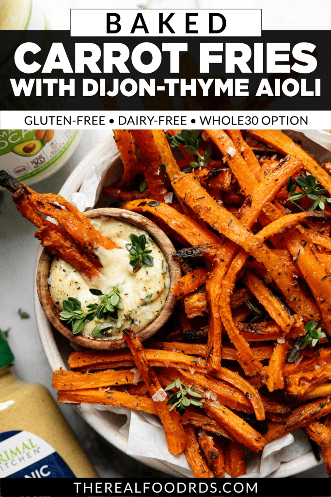 Fresh baked carrot fries being dipped in a bowl of dijon-thyme aioli