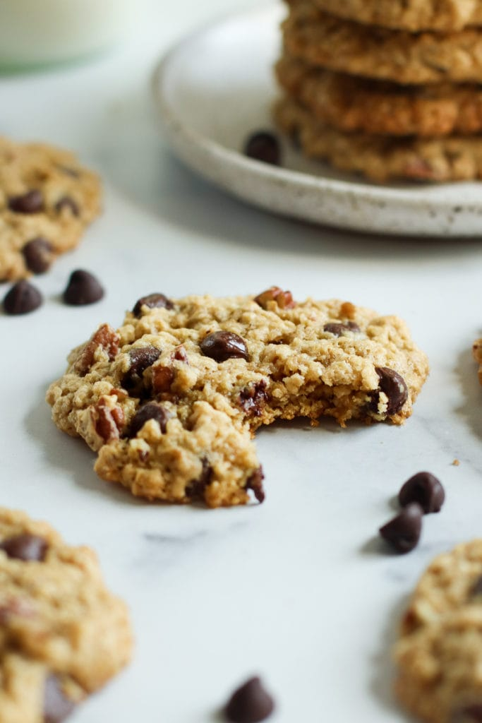 Gluten-free oatmeal chocolate chip cookies with one having a bite taken out of it