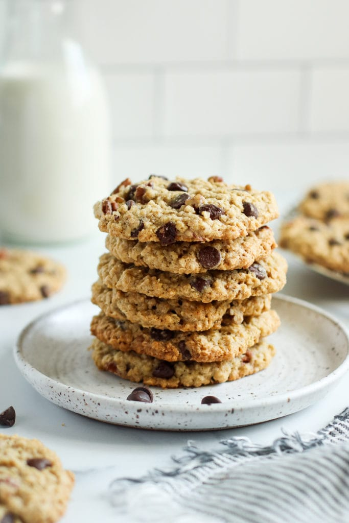 A tall stack of oatmeal chocolate chip cookies on a speckled plate.