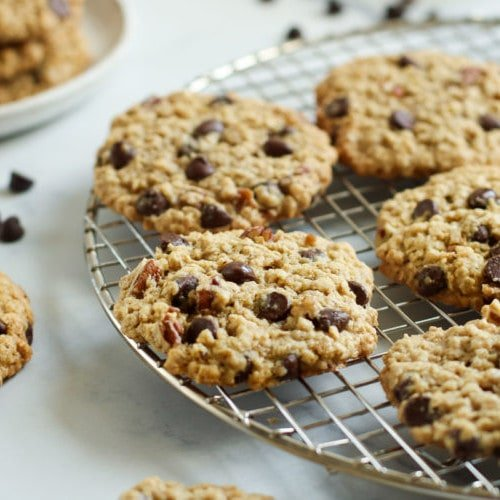 Freshly baked oatmeal chocolate chip cookies on a gold cooling rack