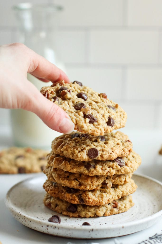 One oatmeal chocolate chip cookie being removed from a tall stack of cookies on a speckled plate