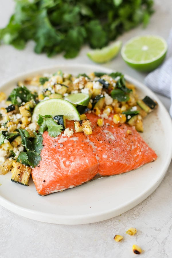 A baked salmon fillet served on a white plate topped with fried corn and zucchini, lime and cilantro.