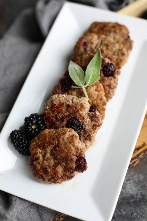 Six blackberry homemade sausages lined up on a white serving tray topped with basil and fresh blackberries