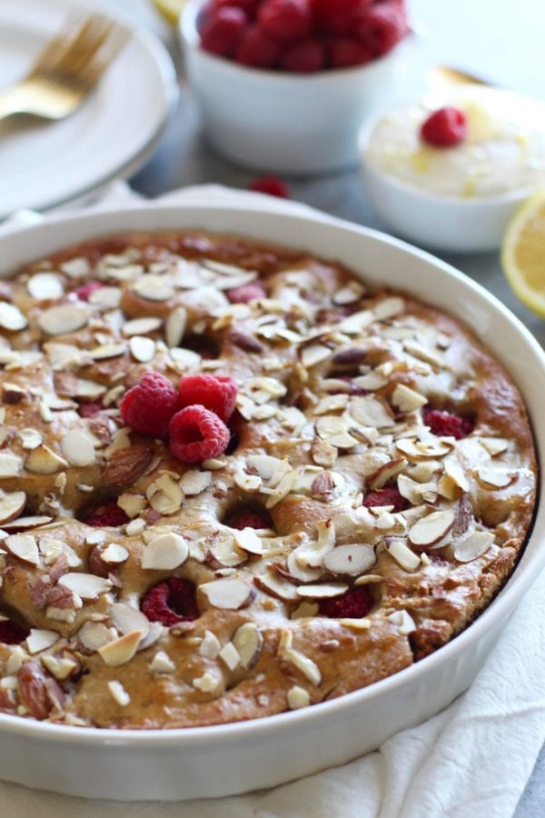 Raspberry Coffee Cake in a white pie plate topped with slivered almonds and fresh raspberries