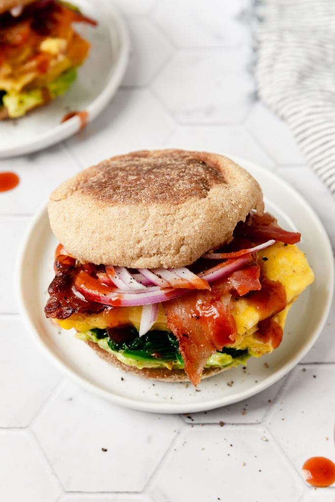 A gluten-free English muffin breakfast sausage filled with bacon, egg, cheese, and hot sauce