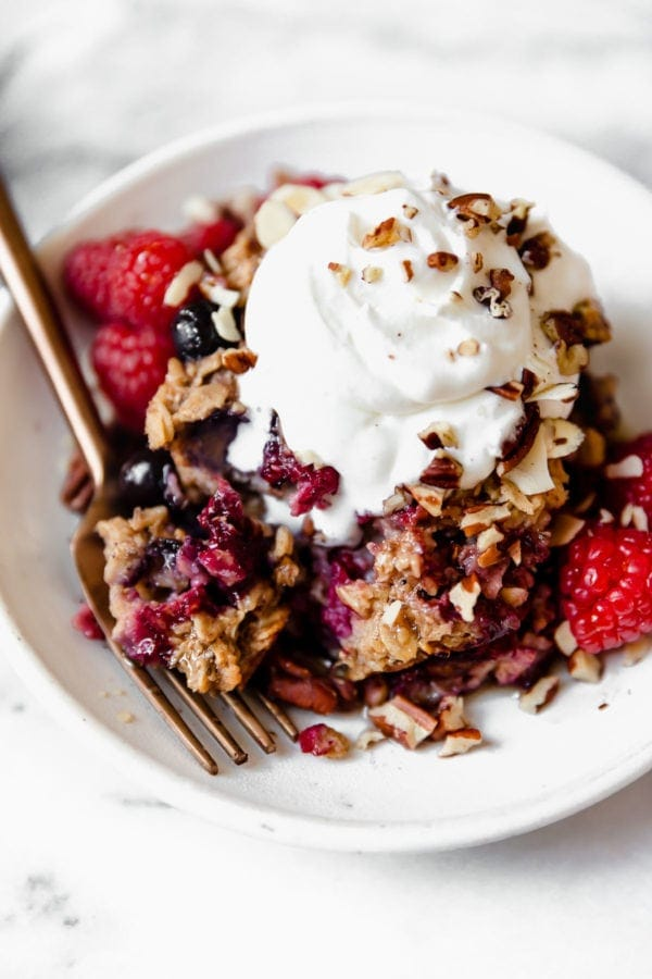 A large serving of mixed berry baked oatmeal on a speckled plate topped with whipped cream, fresh berries, and crushed nuts.