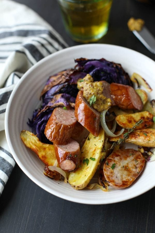 Sheet pan kielbasa with cabbage and potatoes plated on a white plate