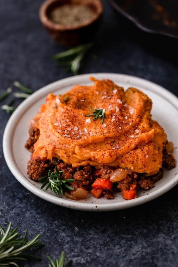 Hearty shepherd's pie topped with creamy sweet potatoes and garnished with rosemary and sea salt on a cream plate