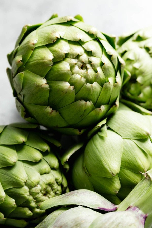 A close up of a raw artichoke leaning against three more artichokes